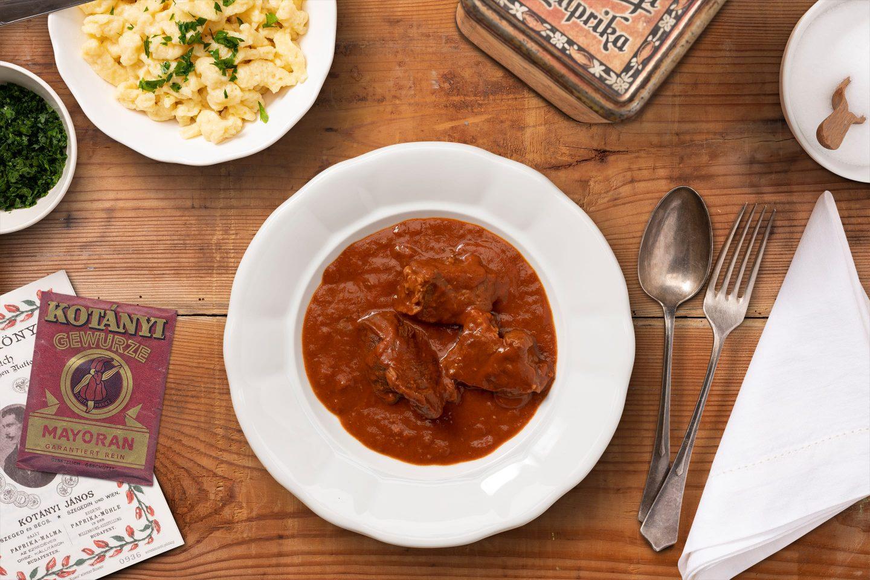 Pun tanjir gulaša i mala činija špecli raspoređeni na tamnom drvenom stolu.