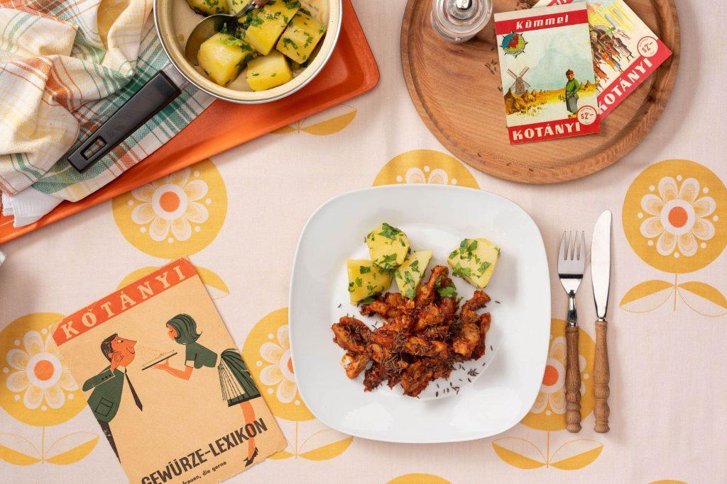Porcija svinjskog mesa začinjenog kimom na blago četvrtastom tanjiru sa krompirom sa peršunom.