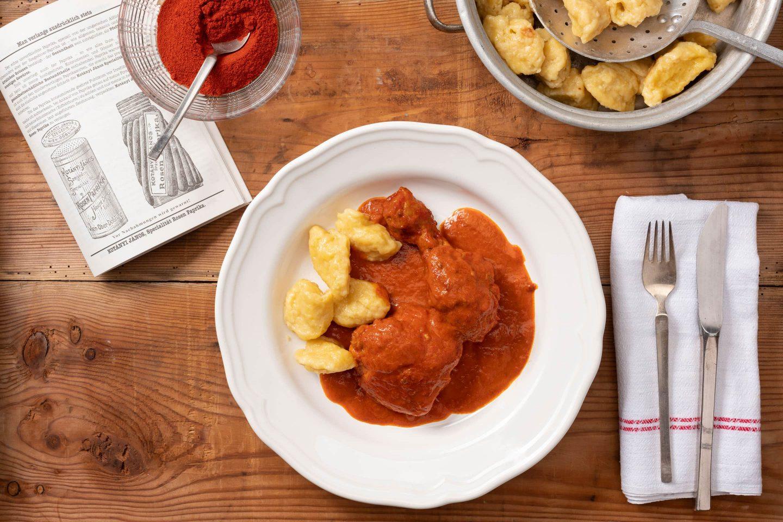 Duboki tanjir sa pilećim paprikašom i knedlama, pored koje je činija puna mlevene začinske paprike.
