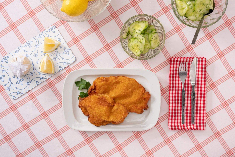 Bečke šnicle servirane sa salatom od krastavca, garnirane mirođijom.